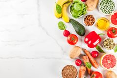Alkaline diet ingredients. Healthy food background, trendy alkaline diet products - fruits, vegetables, cereals, nuts. oils, white marble background above copy Stock Image