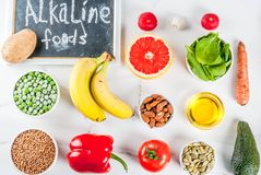 Alkaline diet ingredients. Healthy food background, trendy Alkaline diet products - fruits, vegetables, cereals, nuts. oils, white marble background above copy Royalty Free Stock Image
