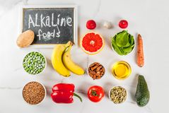 Alkaline diet ingredients. Healthy food background, trendy Alkaline diet products - fruits, vegetables, cereals, nuts. oils, white marble background above copy Royalty Free Stock Photo