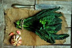 Alkalisk sund mat: grönkålsidor på en tappningbakgrund Arkivbilder