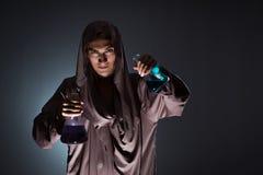 Alkemisten som gör experiment i alkemibegrepp royaltyfria bilder