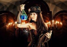 Alkemistkvinnahäxan förbereder dryck, läser den magiska boken Arkivbild