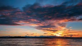 Alki Beach Sunset avec la gamme olympique silhouettée et les réflexions de l'eau n images stock