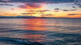 Alki Beach Sunset avec la gamme olympique silhouettée et les réflexions de l'eau n photographie stock