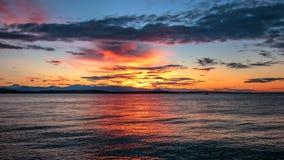 Alki Beach Sunset med Silhouetted olympiskt område och vattenreflexioner n royaltyfria bilder