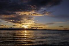 Alki Beach Sunset med Silhouetted olympiskt område och vattenreflexioner n fotografering för bildbyråer