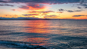 Alki Beach Sunset with Olympic Range Silhouetted and Water Reflections. n stock photography