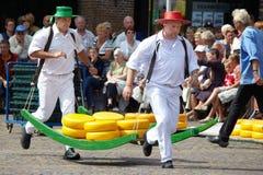 Alkmaar, os Países Baixos - 14 de agosto de 2009: Os portadores do queijo estão deslocando o queijo com uma mostra no mercado tra Fotos de Stock Royalty Free