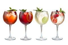 Alkoholów odświeżający koktajle z mennicą, owoc i jagodami na białym tle, Set cztery koktajlu w szklanych szkłach na a fotografia royalty free