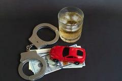 Alkohol, die Handschellen und das Auto spielen auf Farbhintergrund stockfotografie