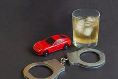 Alkohol, die Handschellen und das Auto spielen auf Farbhintergrund stockfoto