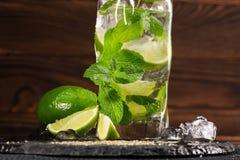 Alkohol och ny mojitodrink med rom, ny limefrukt, mintkaramell, krossad is och socker på en mörk träbakgrund Sommardrycker Royaltyfri Foto