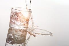 Alkohol som häller i exponeringsglas på vit Royaltyfri Bild