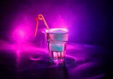 Alkoholcoctail i exponeringsglas med is i rök på mörk bakgrund Klubban dricker begrepp Ett exponeringsglas av coctailen Selektivt royaltyfri foto