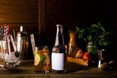 Alkoholcoctail med nya frukter och bär med en flaska av uppiggningsmedel och ett ställe under texten på flaskan på trä Royaltyfria Foton