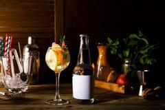 Alkoholcoctail med nya frukter och bär med en flaska av uppiggningsmedel och ett ställe under texten på flaskan på trä Arkivfoto