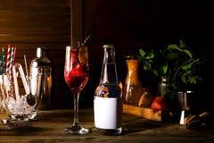 Alkoholcoctail med nya frukter och bär med en flaska av uppiggningsmedel och ett ställe under texten på flaskan på trä Royaltyfri Fotografi