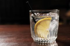 Alkoholdryck med citronen och is på en gammal trätabell royaltyfri fotografi
