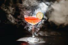 Alkoholiczna koktajl charcica z ajerówką, ajerkoniakiem, grapefruitowym sokiem i lodem, czarny tło, wszystko w dymu, garnirującym fotografia stock