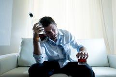 Alkoholiczny Biznesowy mężczyzna jest ubranym błękitnego luźnego krawat pijącego z whisky butelką na leżance fotografia stock