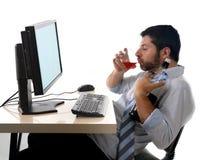 Alkoholiczny biznesowy mężczyzna pije whisky obsiadanie pijącego przy biurem z komputerem zdjęcie stock