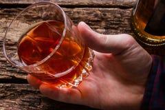 Alkoholiczny mężczyzna trzyma szkło whisky obraz royalty free