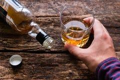 Alkoholiker, der ein Glas Alkohol hält Stockbilder