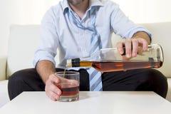 Alkoholiker getrunkener Geschäftsmann in der losen Zeit auf trinkendem Whisky der Couch Stockfoto