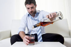 Alkoholiker getrunkener Geschäftsmann in der losen Zeit auf trinkendem Whisky der Couch Stockfotografie