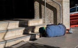 Alkoholiker schläft auf der Straße stockfotografie