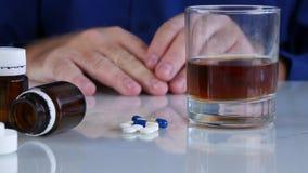 Alkoholische Person vor Alkohol und medizinische Pillen mit Handdem rütteln stock video