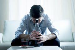 Alkoholischer Geschäftsmann, der die blaue lose Bindung getrunken mit Whiskyflasche auf Couch trägt Lizenzfreie Stockfotografie