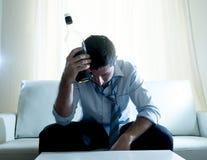 Alkoholischer Geschäftsmann, der die blaue lose Bindung getrunken mit Whiskyflasche auf Couch trägt Stockfoto