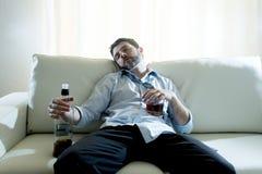 Alkoholischer Geschäftsmann, der die blaue lose Bindung getrunken mit Whiskyflasche auf Couch trägt Stockfotografie