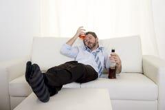 Alkoholischer Geschäftsmann, der die blaue lose Bindung getrunken mit Whiskyflasche auf Couch trägt Lizenzfreie Stockfotos