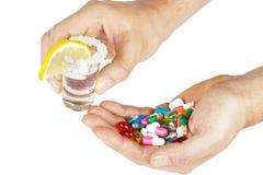 Alkoholisches Getränk mit Medizin mit den Händen auf Weiß Stockfoto