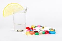 Alkoholisches Getränk und medicals auf Weiß Lizenzfreie Stockfotografie