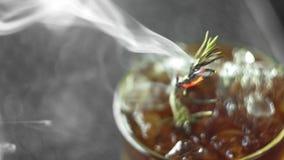Alkoholiserad coctail för förkylning non med citronen, rosmarin, ingefäran och kvass i ett exponeringsglas som är fullt av isfruk stock video