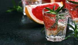 Alkoholiserad coctail med grapefrukten, sodavatten, is, gin och rosmarin, m?rk bakgrund f?r stenst?ngr?knare, selektiv fokus royaltyfri fotografi