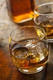 Alkoholiserad whiskybourbon i ett exponeringsglas med is royaltyfri bild