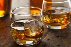 Alkoholiserad whiskybourbon i ett exponeringsglas med is Fotografering för Bildbyråer