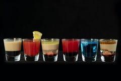 Alkoholiserade coctailskott för blandning samman med isolerad svart bakgrund royaltyfri bild
