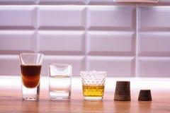 Alkoholiserade starka drinkar i exponeringsglas på bakgrunden royaltyfria bilder