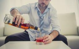 Alkoholist drucken affärsman i lös tid på soffan som dricker whisky Arkivbild