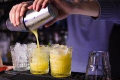 Alkoholisten som den gula coctailen är, häller Fotografering för Bildbyråer
