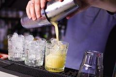 Alkoholisten som den gula coctailen är, häller Arkivfoto