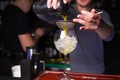Alkoholisten som den gula coctailen är, häller Arkivbild