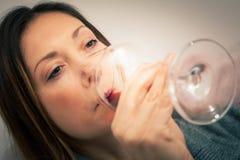 Alkoholizm, kobieta pije szklanego czerwone wino strona Obraz Stock