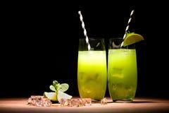alkoholmojitococtailar med limefrukt- och iskuber på tabellen royaltyfri foto