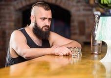 Alkoholu uzależniony pojęcie Modnisia brutalny mężczyzna pije alkohol rozkazuje więcej napoje przy baru kontuarem Alkoholizm i zdjęcia stock